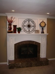 We covered this brick hearth in marble, added a new gas insert, and finished with a custom wood mantelpiece.