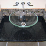 Contemporary design for a powder room includes a marble surround and a granite top featuring a chiseled edge.