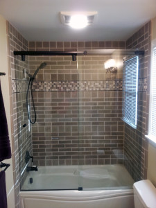 Handmade tiles installed over a MAAX tub. Hydroslide shower-glass also setup by The Home Artisan Group.