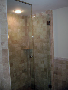 Natural marble and frameless shower glass.