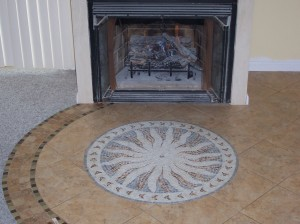 Curved tile work acts as a transition to the carpet and compliments custom sunburst medallion in front of a gas fireplace.