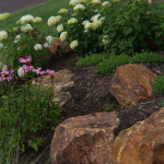 Boulders help hold the slope of this planting bed together.