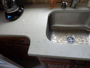 Corian tops with a stainless steel bowl. Corian can have the sink welded to the top with zero seam.