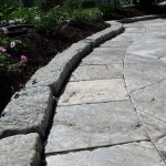 Detail work of a gray travertine patio with a belgian block border.