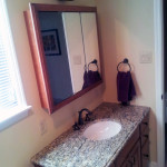 Giallo ornamental granite top on a semi-custom vanity with matching medicine cabinet. Also added a new fixture by Progress and a faucet by MOEN.
