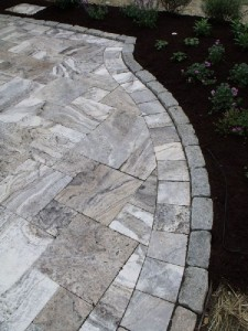 Gray travertine with a belgian block border.
