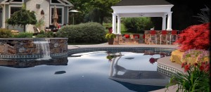 A hot tub that cascades into a tiled pool, a covered porch plus beautiful plants = a resort in your backyard.