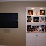 Ran wall wiring for surround sound and data, built cabinet to the right and lit it from the top. Everything is remote controlled even though the components are not visible.