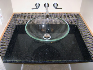 Small marble tiles to accent a powder room sink.