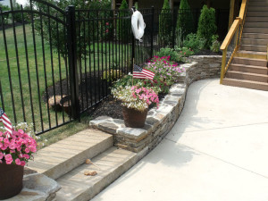 Small retaining wall and estate fence to seperate the yard from the pool area.