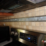 Travertine, metal and glass joining together to make a dramatic back splash.